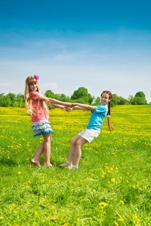 niños bailando: Dos niñas amigos de la mano y bailando en el campo de diente de león