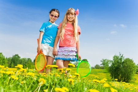 Two beautiful girls with tennis racquets standing in flower field photo