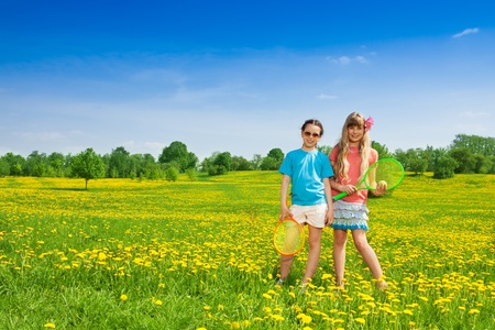 Two beautiful 10 year old girls with tennis racquets standing in flower field photo