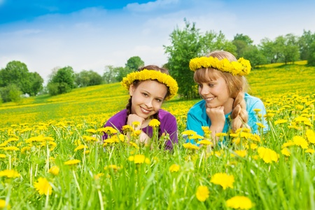 Two happy beautiful smiling girl laying in dandelion yellow flower field wearing wreath photo