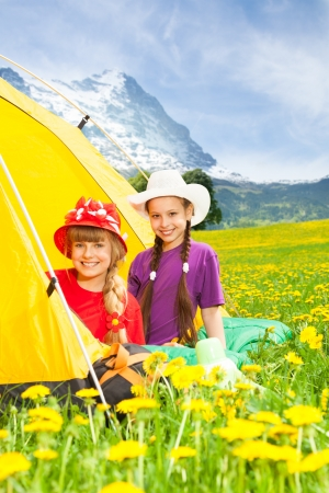 Two happy little smiling girls in summer hats laying in a tent staying in mountains photo