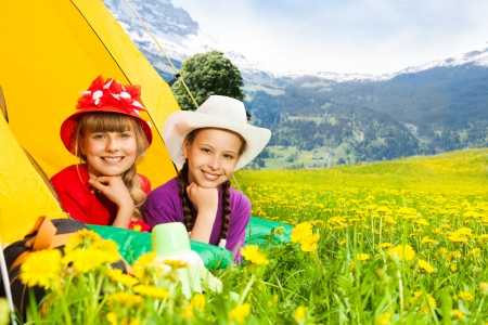staying: Two happy little smiling girls laying in a tent staying in mountains Stock Photo