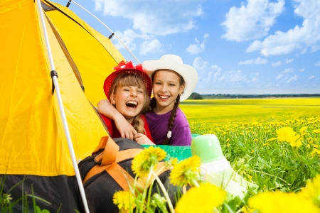 Two happy laughing little girls in camping tent in dandelion field photo