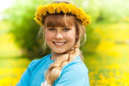 Close-up of beautiful blond girl wearing wreath made of dandelions photo