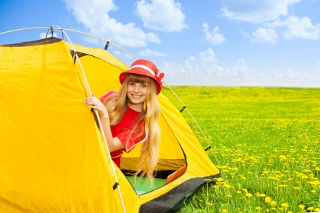 Blond happy laughing little 10 years old girl sitting in camping tent in mountain yellow field photo