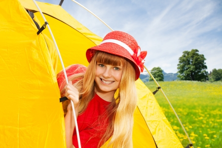 Close portrait of blond happy laughing little 10 years old girl sitting in camping tent in mountain yellow field photo