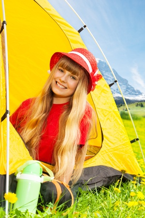 Portrait of blond happy smiling little years old girl sitting in camping tent in yellow dandelion field photo