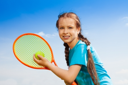 Beautiful brunet 10 years old little girl with tennis racquet photo