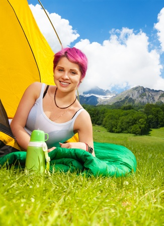 Beautiful young woman with red hair in a tent smiling, on her hiking trip photo