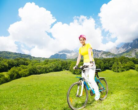 Happy young woman in bright clothes with red hair riding a bike photo