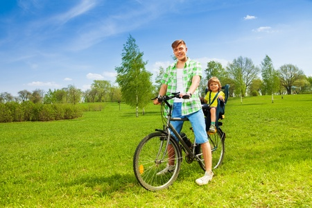 child seat: Young man on the bike with little boy in child seat Stock Photo