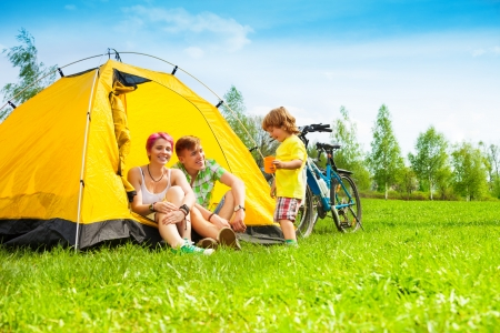 Young couple with kid sitting in the tent on a bike hiking trip photo