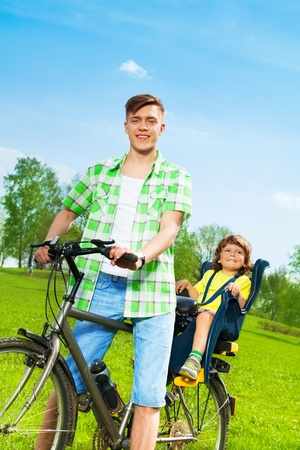 child seat: Young father with son in child seat of a bike Stock Photo