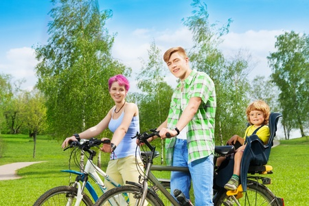 child seat: Young family on the bikes with kid in child seat riding in the park