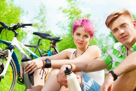 Two young people sitting with water bottles and bikes photo