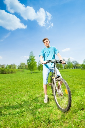 Happy young man sitting on the bike in park photo