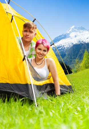 Young happy smiling couple sitting in a tent on a mountain field in Switzerland photo