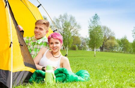 Young man and woman sitting in the tent in the park on sleeping bag photo