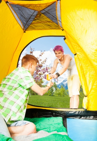 Woman giving cup of tea to her boyfriend in the tent on hiking trip in mountains photo