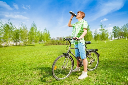 Young man sitting on a bike and drinking water from bottle photo