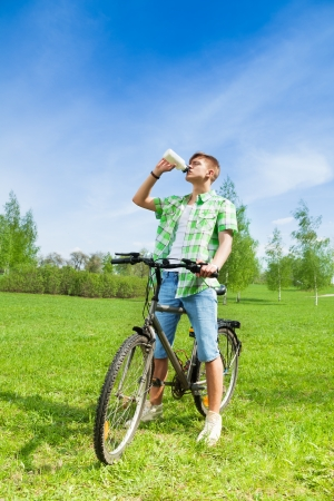 Young man sitting on a bike and drinking water in a bottle in a park photo