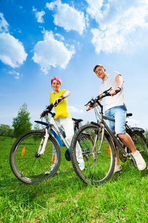 Young happy couple on the bikes together on the green field in park photo