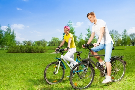 Two young people, man and woman riding a bike in the park photo