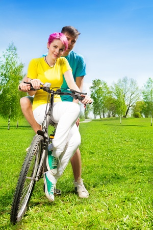 Couple sitting on the one bike hugging and smiling photo