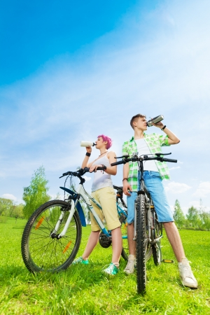 Young couple on the bikes drinking water from the bottles photo