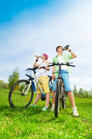 Young couple, man and woman on the bikes drinking water from the bottles photo