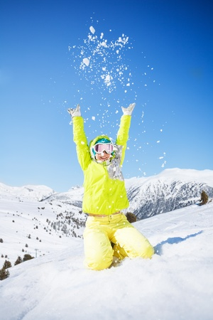 Cute happy young woman in green ski outfit throwing snow in the air photo