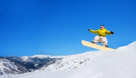 salto largo: Snowboarder hombre guapo lindo saltando de cama elástica en snowboard en el parque de esquí en montaña
