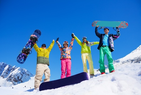 hand lifted: Happy friends men and women stand in snow with snowboards lifting and waving hands