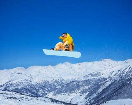 salto largo: Hombre snowboarder hermoso fresco que la celebración de snowboard en el aire saltando con montañas de fondo