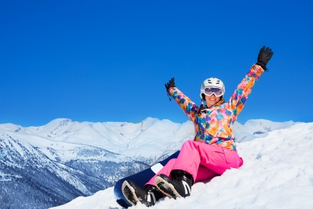 Happy excited woman in pink sit on snow holding snowboard with lifted hands photo