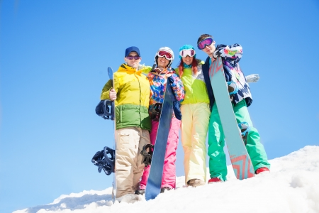 Four happy friends hug and hold snowboards standing in snow in winter Stock Photo