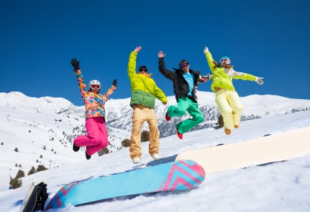 Four snowboarders friends in bright vivid clothes jumping in snow with mountains on background Stock Photo