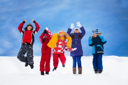 lifted hands: Group of five happy kids jumping in snow with lifted hands Stock Photo