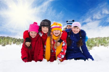 Five happy laughing kids, hugging together and diversity looking at winter photo