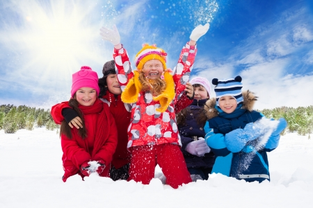 Group of five happy kids, boys and girls throw snow in the air photo