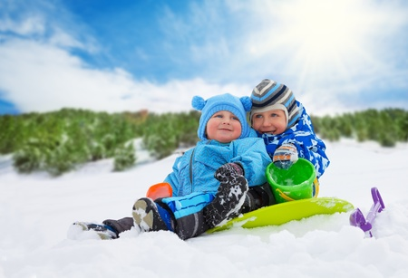 Two little boys brothers sitting on the snow and playing together on winter day photo
