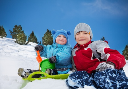 Two brothers sitting on the snow and playing together on winter day photo