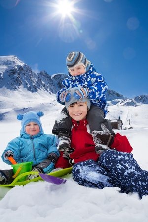 Three happy brothers sitting in snow park outside in winter photo