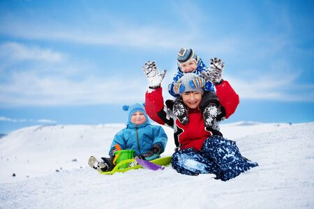 Three brothers sitting on the snow and playing together on winter day photo