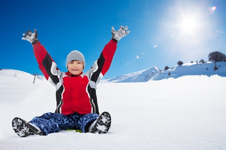 Happy exited boy sitting on sled with her hands lifted,, in the mountains photo