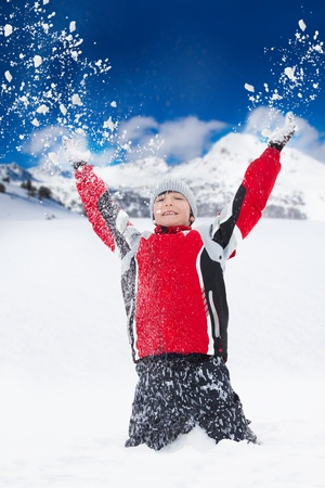Happy smiling boy throws snow in the air with snowflakes flying in all directions photo