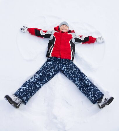Happy boy in red bright vivid clothes laying in star shape photo