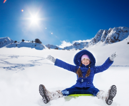 Happy smiling girl sitting on sled with her hands lifted expressing excitement, in the mountains photo