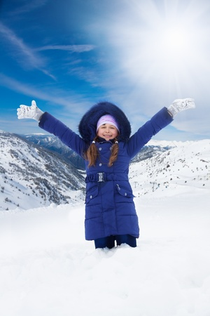 8 years old: Happy 8 years old Caucasian girl in blue sitting with lifted from excitement hands on snow outside in winter Stock Photo