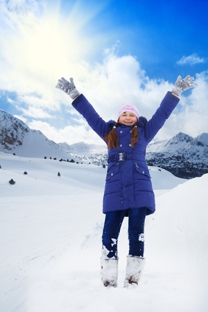 Happy 8 years old Caucasian girl in blue standing with lifted from excitement hands on snow outside in winter photo